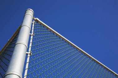metal post with a chain link security fence against a blue sky