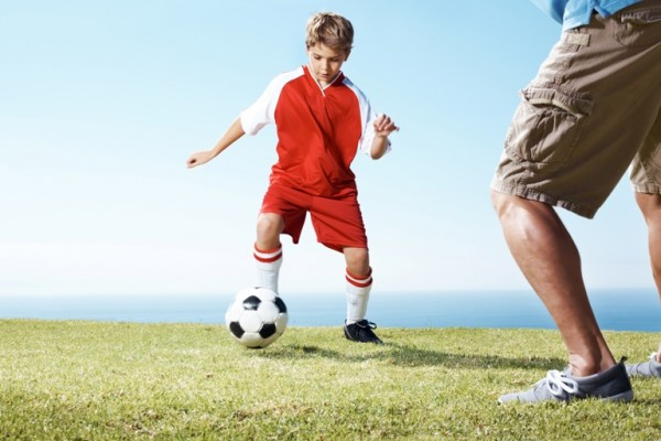 Small boy playing a soccer game with a man
