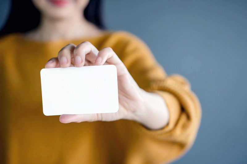 Woman holding blank business card for mock up